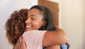 Loving Senior Mother Hugging Adult Daughter Indoors At Home