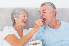 Loving senior woman feeding cereals to husband Royalty Free Stock Image