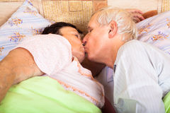 Loving seniors kissing in bed Stock Images