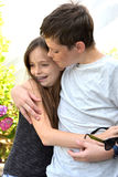 Loving siblings. Happy siblings embracing each other, the brother wants to protect his younger sister Stock Photos