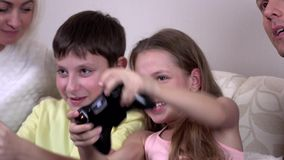 Loving siblings playing video game in the living room. Cheerful brother and sister playing video games in the sofa at home, pink shirt and a yellow T-shirt stock video