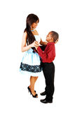 Loving sister and brother. A big sister in a blue dress holding the head of her little brother, standing Stock Photo