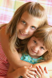 Loving Sisters. Two cute young loving sisters with arms around each other Royalty Free Stock Photos