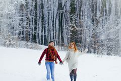 Loving smiling couple is having fun while running along the snowy forest. Stock Images