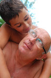 Loving son and dad. Portrait of boy dearly hugging his aged bald daddy Royalty Free Stock Images