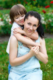 Loving son hugging his happy mother in park Stock Photo