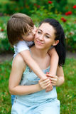 Loving son hugging and kissing his happy mother in. Park Royalty Free Stock Images