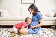 Son Kissing Abdomen Of Pregnant Mom In Living Room. Loving son kissing abdomen of pregnant mom on carpet in living room at home Stock Photos