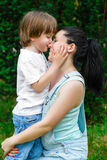 Loving son kissing his happy mother on the nose.  Royalty Free Stock Photography