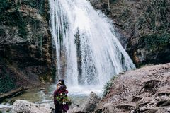 A loving, stylish, young couple in love on the background of a waterfall. stock photo