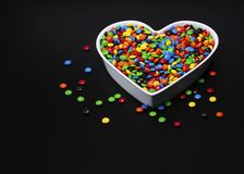 Loving sweet candy snacks. White shaped ceramic bowl filled with small colorful round coated candies on a black background with text space. Concept: loving royalty free stock photo