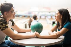 Teen Couple Having A Date In Bowling Alley. Loving teen couple having a date in bowling alley at club royalty free stock photos