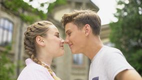Loving teen couple nuzzling, first love, couple looking at each other, emotions