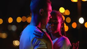 Loving teenage couple embracing in night lights, enjoying romantic atmosphere. Stock footage stock footage