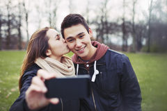 Loving teenage couple taking self portrait Stock Images