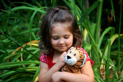 Loving Tiger. Four year old girl cuddling with her stuffed animal tiger. She has a smile on her face and is looking at her tiger Royalty Free Stock Image