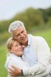 Loving trendy senior couple embracing outdoors Royalty Free Stock Photos