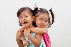 Loving twin sisters two years outdoors. Playing Royalty Free Stock Images