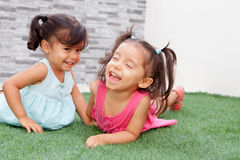 Loving twin sisters two years outdoors playing. On the grass Royalty Free Stock Photography