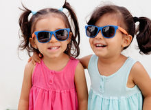 Loving twin sisters two years with sunglasses outdoors. Playing Stock Photo