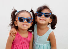 Loving twin sisters two years with sunglasses outdoors Stock Image