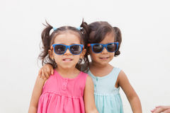 Loving twin sisters two years with sunglasses outdoors. Playing Royalty Free Stock Image