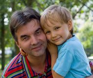 Loving Uncle And Nephew. Portrait of smiling uncle and young nephew embracing.  Nephew is leaning on the shoulder of his uncle.  Taken outdoors in a wooded area Stock Photo