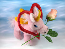 Loving unicorn. Romantic pink unicorn with rose and heart on blue background Stock Image