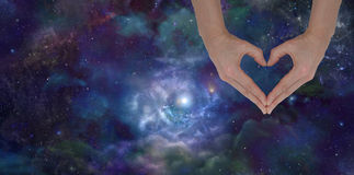 Loving the Universe. Female hands forming heart shape laid over deep space banner background Royalty Free Stock Photo
