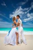Loving wedding couple on beach. In white dresses Stock Images