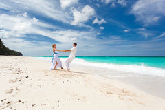 Loving wedding couple on beach. Loving wedding couple dancing on beach in white dresses Royalty Free Stock Photography