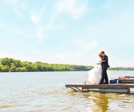 Loving wedding couple embarcing near water Royalty Free Stock Photo