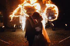 Loving wedding couple kissing and watching fire-show. Kissing wedding couple at night and fire-show on their honor. Burning heart Stock Photo