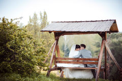 Loving wedding couple is sitting on a bench Stock Image