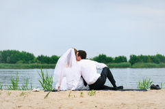 Loving wedding couple sitting and kissing near water Royalty Free Stock Images