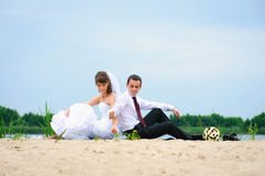 Loving wedding couple sitting near water and strew sands Stock Photography