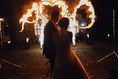 Loving wedding couple  watching fire-show. Loving wedding couple watching fire-show on their honor. Night,burning heart Stock Photography