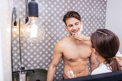 Loving wife helping her sexy husband using shaving foam. Helpful wife. Loving dark-haired wife helping her sexy husband using shaving foam in the morning royalty free stock photos