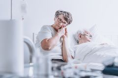 Loving wife at hospital bed. Loving wife sitting at her husband`s hospital bed and holding his hand Royalty Free Stock Images