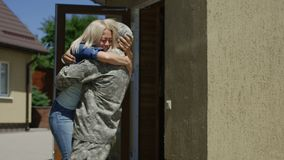 Loving wife meeting soldier at home. Cheerful woman running out of house and embracing military husband back at home excited with happiness stock footage