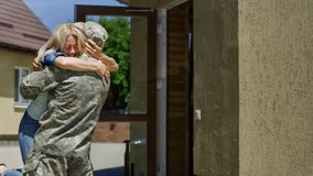 Loving wife meeting soldier at home stock photography