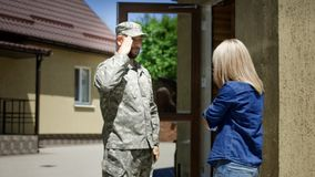 Loving wife meeting soldier at home. Cheerful women running out of house and embracing military husband back at home excited with happiness royalty free stock images