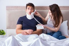 The loving wife taking care of injured husband in bed. Loving wife taking care of injured husband in bed Stock Image