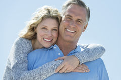 Loving Woman Embracing Man From Behind Against Clear Sky Stock Photography