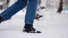 Loving woman feet walk to meet her partner in a park on snowfall. Romantic couple on dating enjoying snowy winter day stock footage