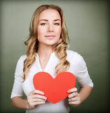 Loving woman with red heart. Portrait of cute loving woman holding in hands red paper heart, isolated on gray background, Valentine day, love concept Royalty Free Stock Photo