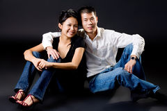 Loving young asian couple. Loving young couple sitting together on the floor Royalty Free Stock Image