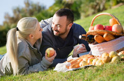 Loving young beautiful couple chatting as having picnic Stock Photo