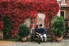 A loving young beautiful couple of students from Europe sits on a park bench in autumn. Close feelings and emotions. Between people stock photos