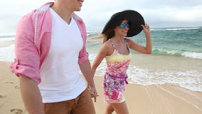 Loving young Caucasian couple holding hands walking together beach Oahu Hawaii. Romantic couple in love holding hands on walk on beautiful summer on hawaiian stock video footage